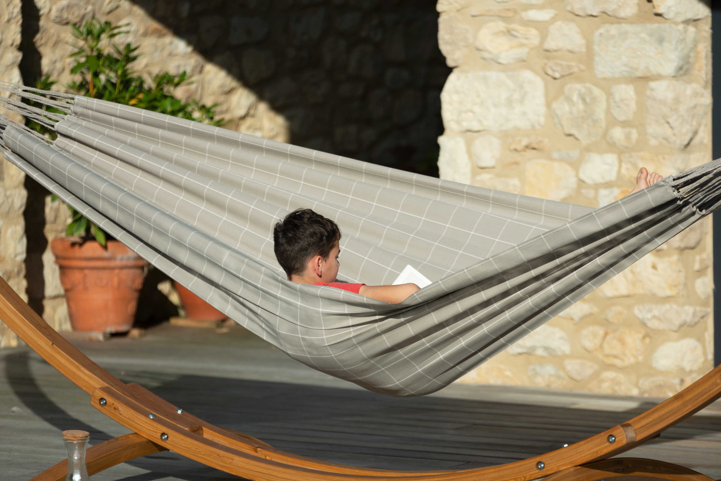 Relaxing poolside on the patio deck in the Brisa Almond Weather-Resistant Hammock